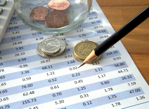 Statement with transactions and glass jar containing coins next to calculator and pencil