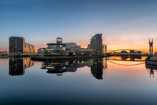 range sunrise at Salford Quays with blue sky and clear reflections in canal.